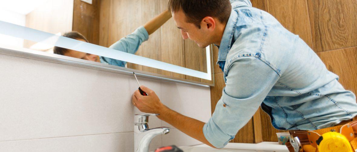 Man installing a mirror on wall in his renewed bathroom